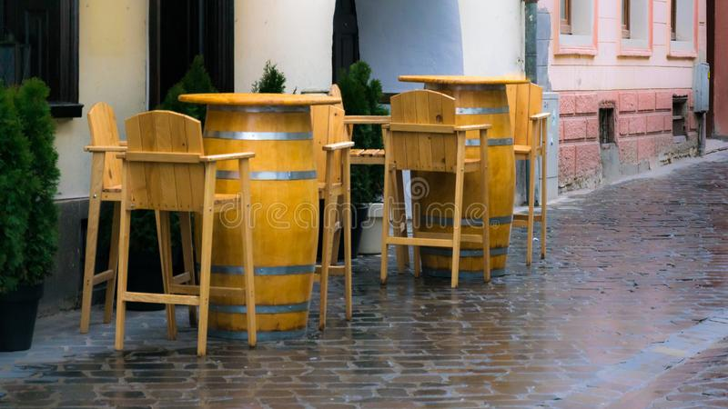Empty wooden chairs and tables barrels on street on rainy day royalty free stock images