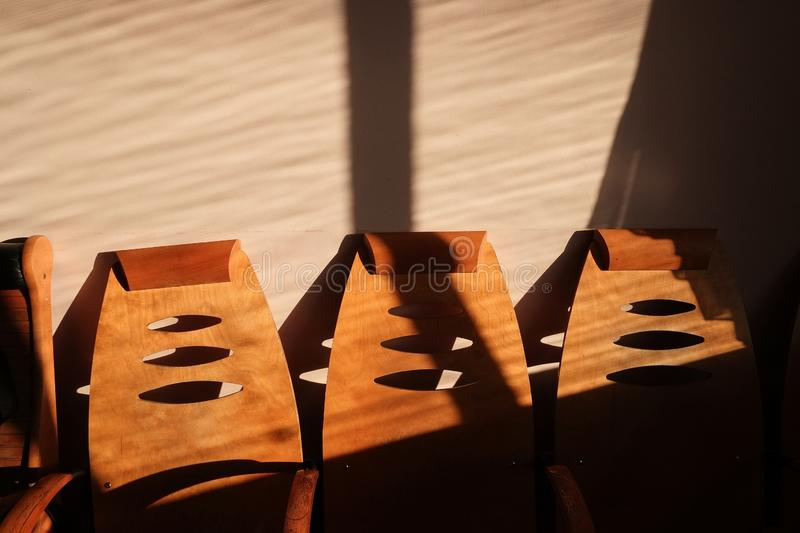 Empty wooden chairs in waiting hall of railway station. Morning sunny light with shadows stock photo