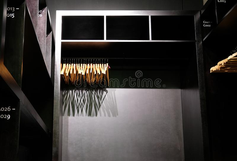 Empty wooden clothes hangers hanging in closet and casting deep shadows. Empty wooden clothes hangers hanging in black closet and casting deep shadows stock photography