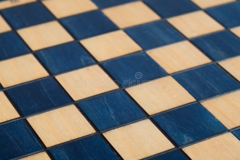 Empty wooden dark blue chessboard. Wooden white blue chess set stock photo