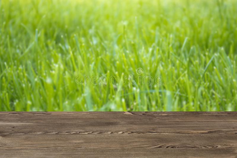 Empty Wooden Deck Table Against Blurred Green Grass Background ...