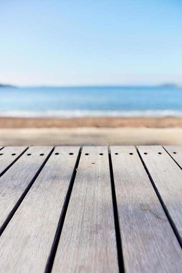 Empty wooden deck table on blurry sea and beach background. Copy space for product display and composite images stock image