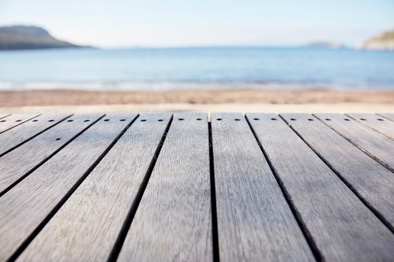 Empty wooden deck table on blurry sea and beach background. Copy space for product display and composite images stock photography