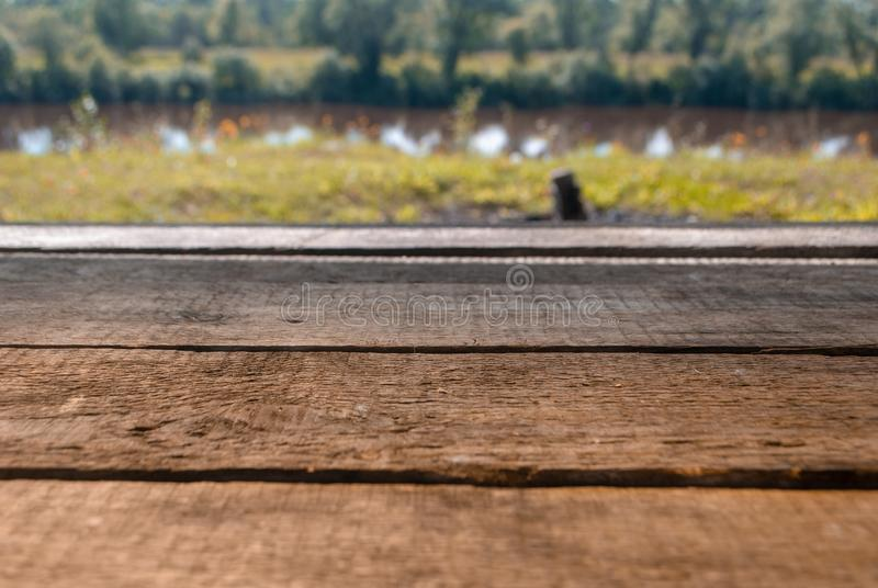 Empty wooden deck table with foliage bokeh background. Ready for product display montage. royalty free stock images