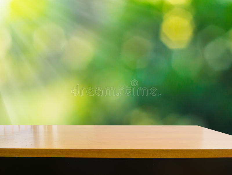 Empty wooden deck table with foliage bokeh background stock photography