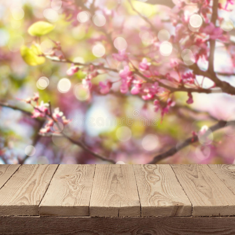 Empty wooden deck table over blooming tree bokeh background for product montage display. Spring concept royalty free stock images