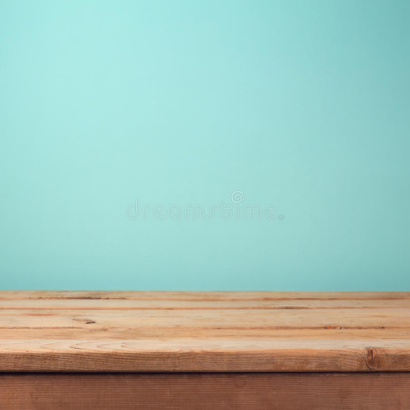 Empty wooden deck table over mint wallpaper background. Empty wooden deck table over mint retro wallpaper background stock photo