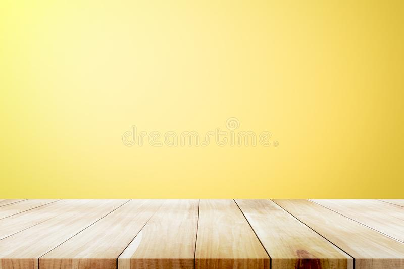Empty wooden deck table over yellow wallpaper background. Empty wooden deck table over yellow wallpaper background for present product royalty free stock photo