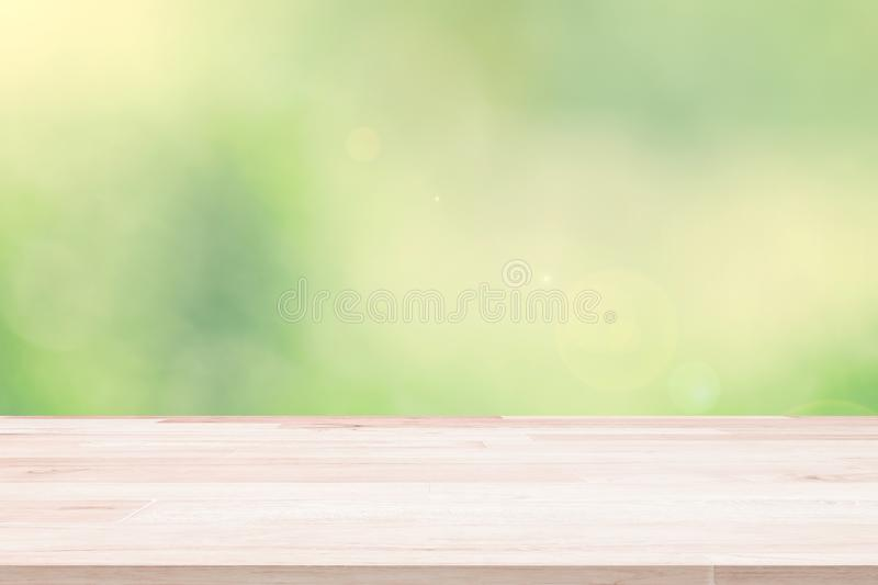 Empty wooden deck table top on green blurred abstract background from foliage background. Ready used us display or. Montage products design royalty free stock image