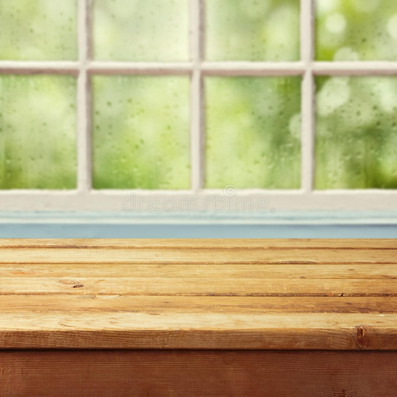 Empty wooden deck table and window with rain drops royalty free stock photography