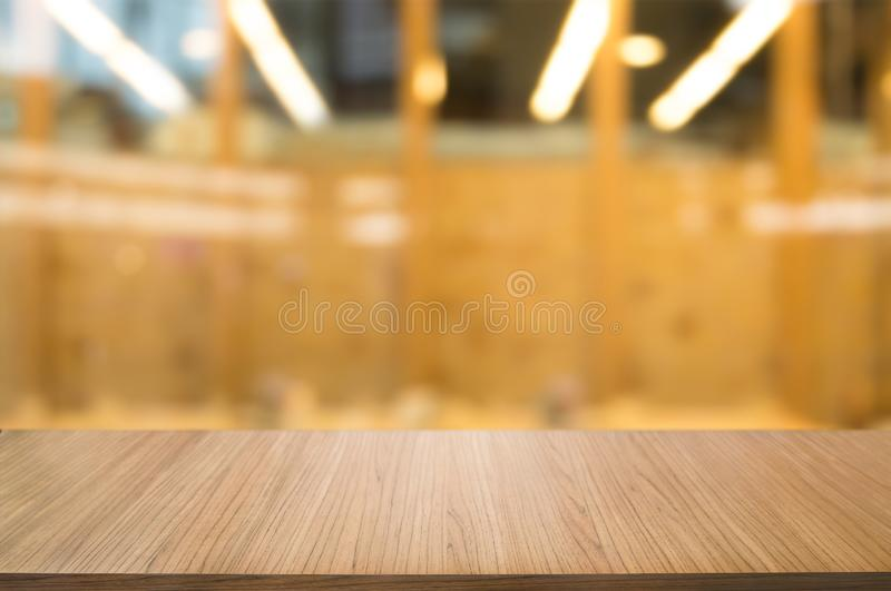 Empty wooden desk over blurred coffee shop cafe background royalty free stock photos