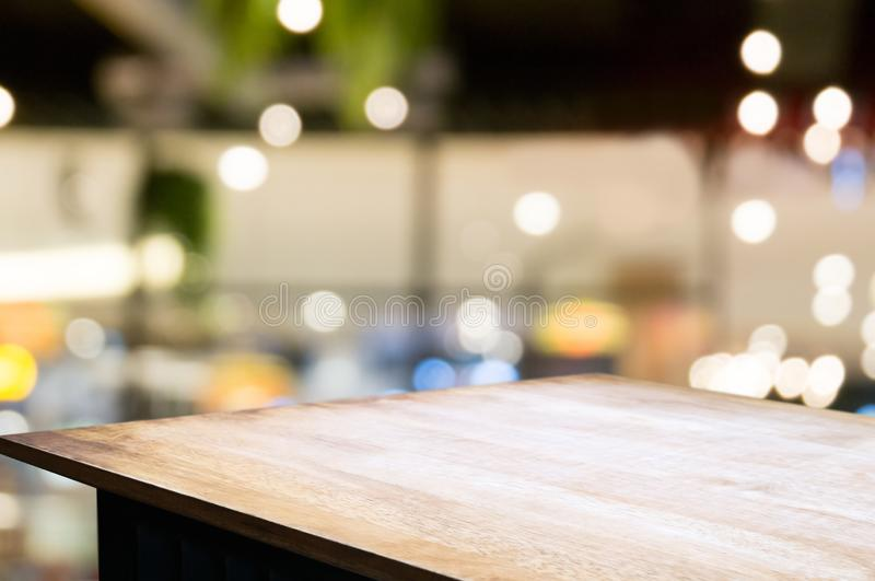 Empty wooden desk over blurred coffee shop cafe background stock photo