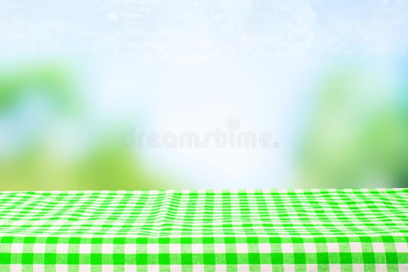 Empty wooden desk table with green checkered tablecloth over abstract bright light blue green spring or summer background. Template for your food and product stock photo