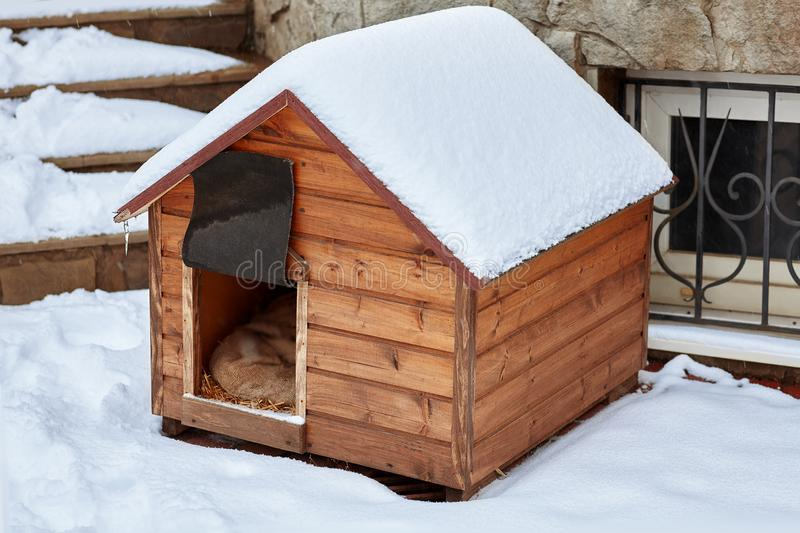 An empty wooden dog house in the winter on the back yard, covered with snow. stock photography
