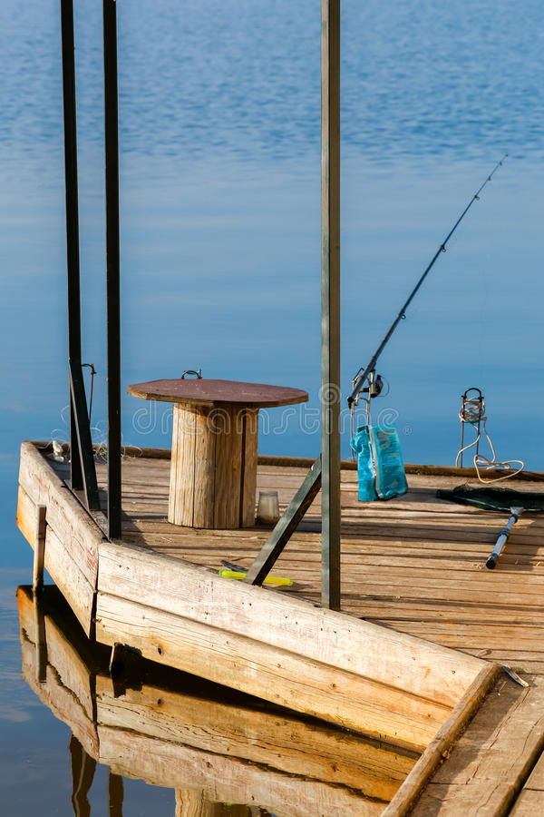 Empty wooden fishing pier with rods, table and bait. Beautiful reflection in a water.  stock photo