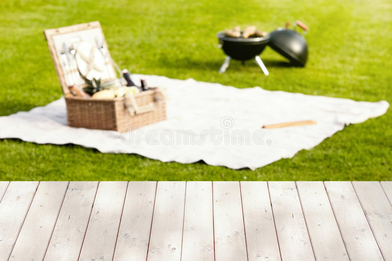 Empty wooden picnic table with hamper and BBQ. Empty wooden picnic table with an open wicker hamper on a rug and BBQ in the background on a green lawn conceptual royalty free stock image