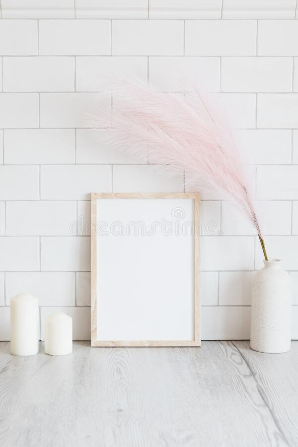 Free Empty Wooden Picture Frame Mockup, Candles, Pink Dried Flowers In Vase On Table. White Tiles Wall Background. Minimal, Elegant, Stock Image - 215690381