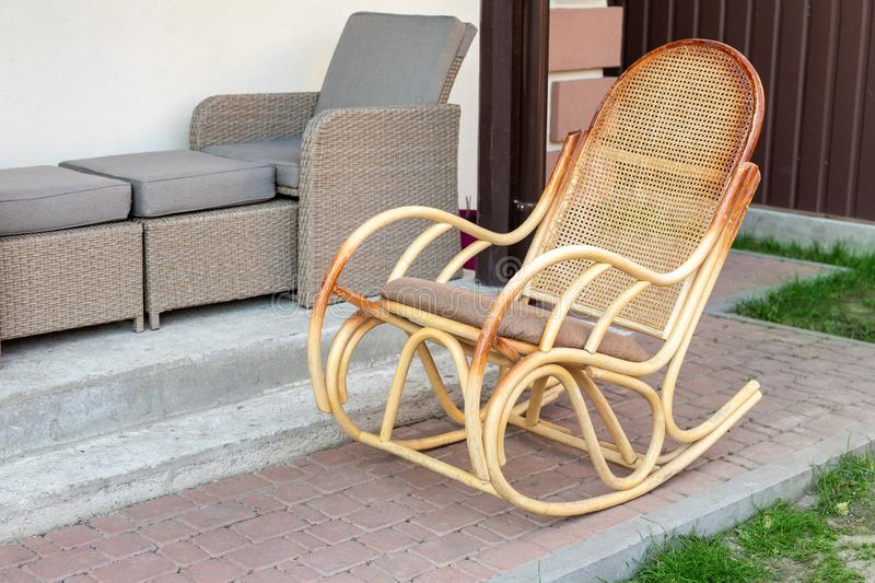 Empty wooden rattan rocking chair on house terrace backyard outdoors. Peaceful lifestyle home exterior. Relax summer furniture nobody leisure travel porch deck stock image