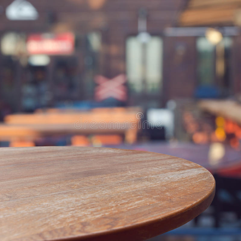 Empty wooden round table over outdoor restaurant background stock photo