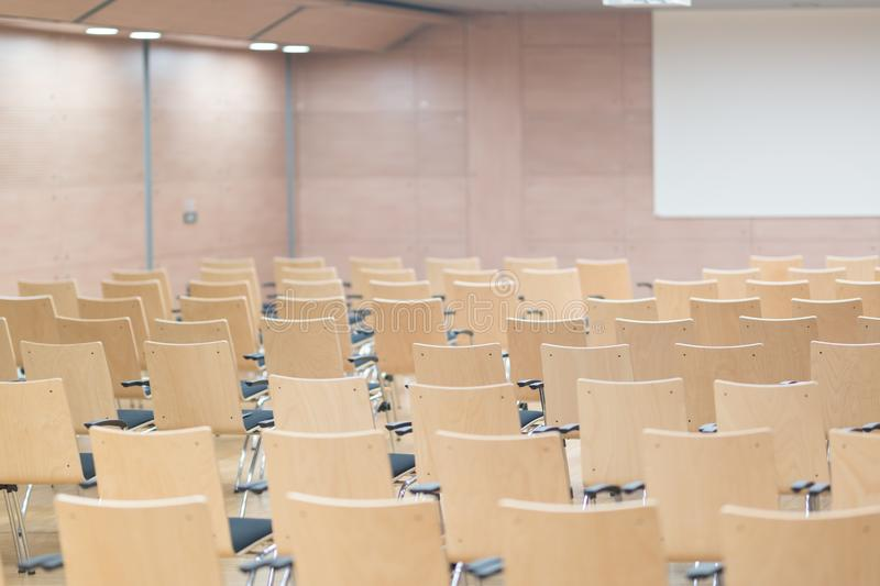 Empty wooden seats in a cotmporary lecture hall. royalty free stock images