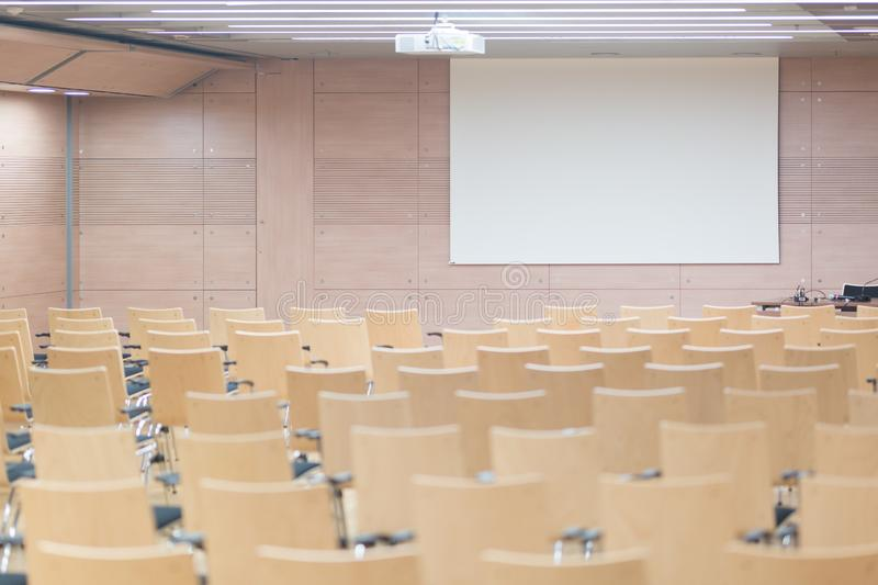 Empty wooden seats in a cotmporary lecture hall. royalty free stock photography