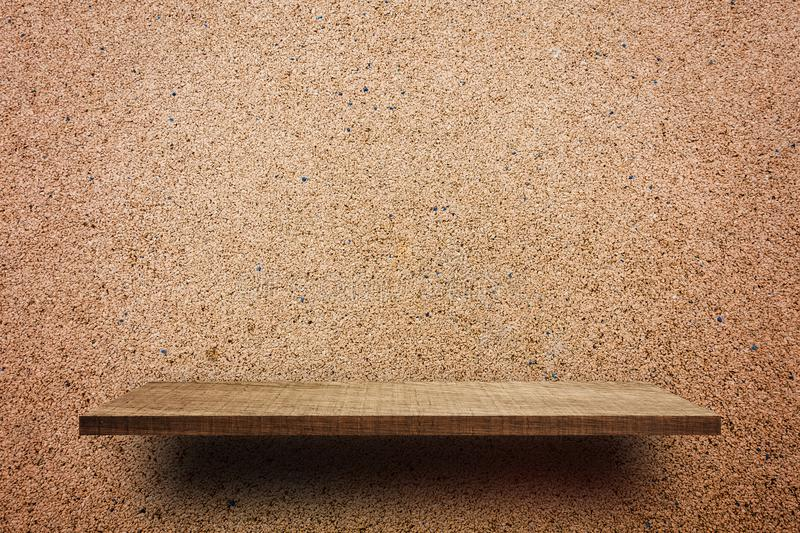 Empty wooden shelf on brown rock wall for display stock image