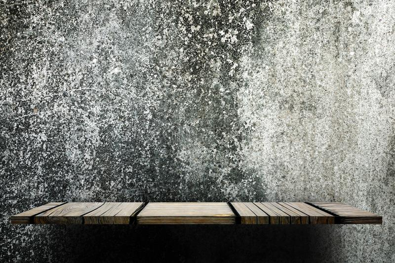 Empty wooden shelf counter on grungy concrete wall for display stock photo