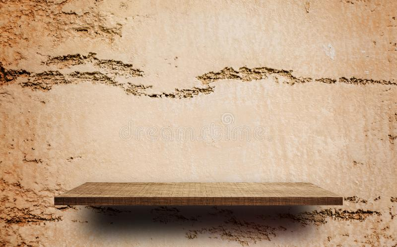 Empty wooden shelf on Cracked Brown cray wall royalty free stock photo
