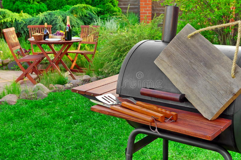 Empty Wooden Signboard Hanging On Barbecue Grill Appliance, Par. Empty Wooden Signboard Hanging On Barbecue Grill Appliance, Grilling Tools And Wooden Table With royalty free stock image