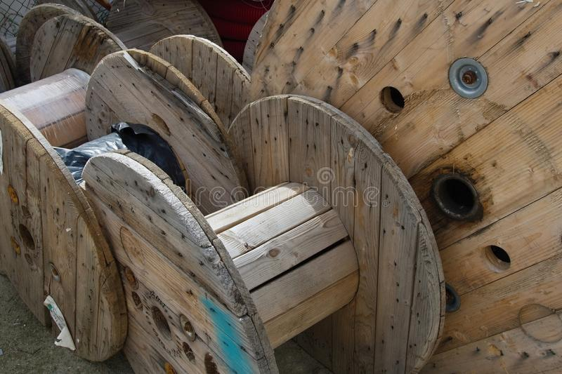 Empty wooden spools for electrical cables. Used, empty wooden spools for electrical cables deposited in the yard of a building company. Close-up view royalty free stock images