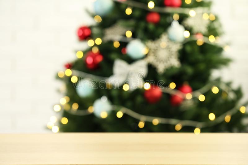 Empty wooden table against fir tree with Christmas lights. Space for design. Empty wooden table against fir tree with Christmas lights, blurred view. Space for stock photography