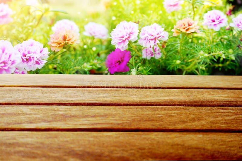 Empty wooden table on beautiful flower garden stock image
