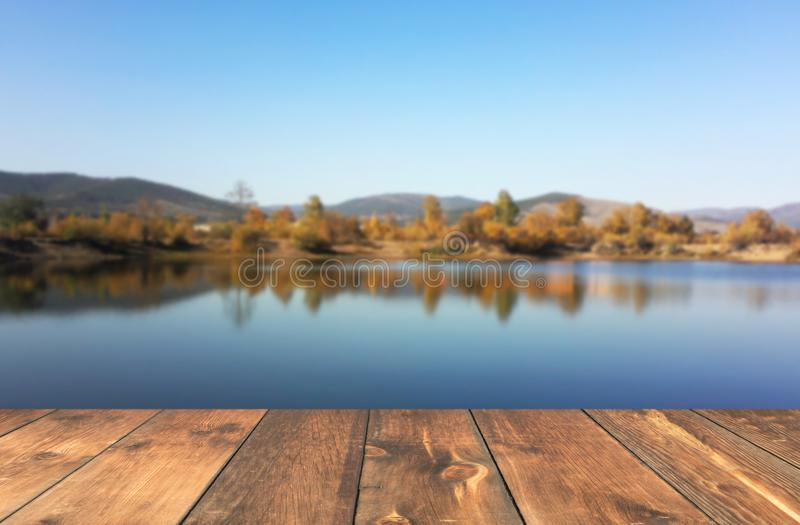 Empty wooden table blured lake. Landscape stock images