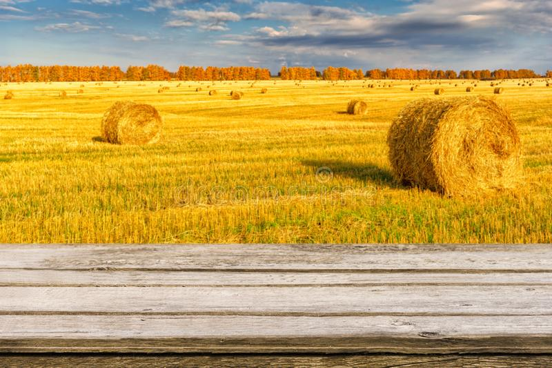 Empty wooden table with blurred autumn landscape of beveled field and straw bales. Mock up for display or montage products. Empty wooden table with blurred stock photo