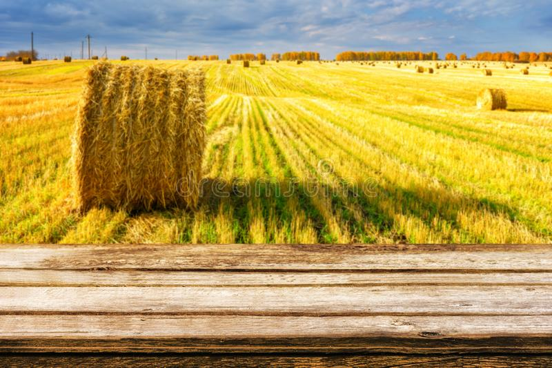 Empty wooden table with blurred autumn landscape of beveled field and straw bales. Mock up for display or montage products. Empty wooden table with blurred royalty free stock images