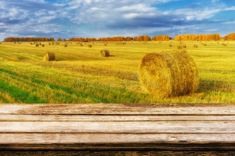 Empty wooden table with blurred autumn landscape of beveled field and straw bales. Mock up for display or montage products royalty free stock photo
