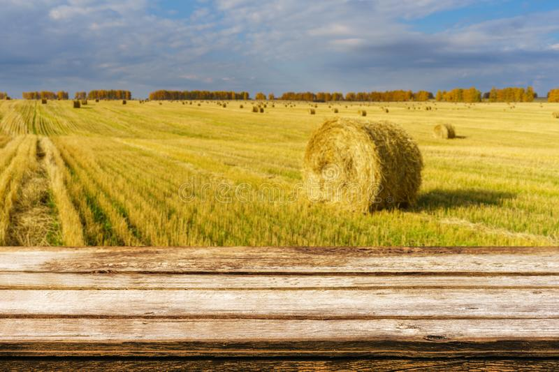 Empty wooden table with blurred autumn landscape of beveled field and straw bales. Mock up for display or montage products royalty free stock photos