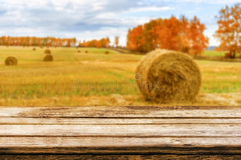 Empty wooden table with blurred autumn landscape of beveled field and straw bales. Mock up for display or montage products royalty free stock photography
