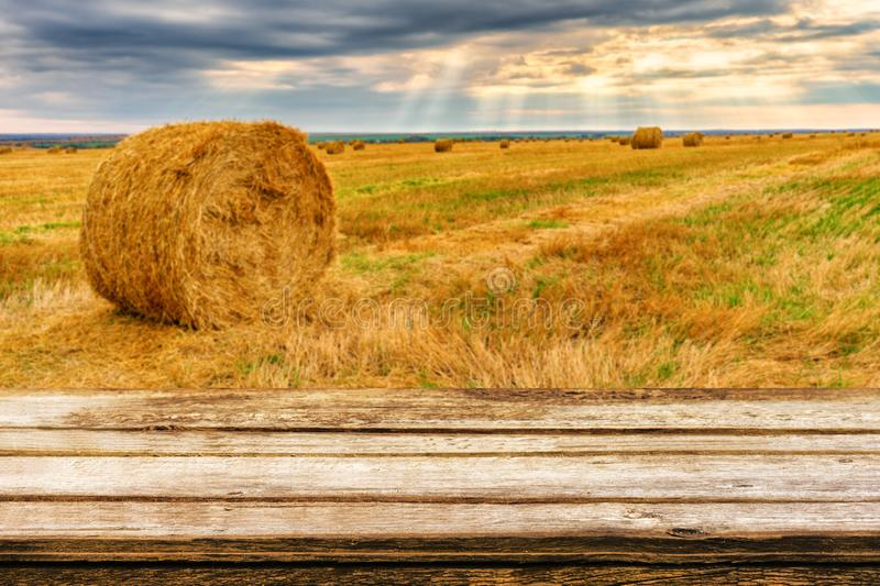 Empty wooden table with blurred autumn landscape of beveled field and straw bales. Mock up for display or montage products stock photography
