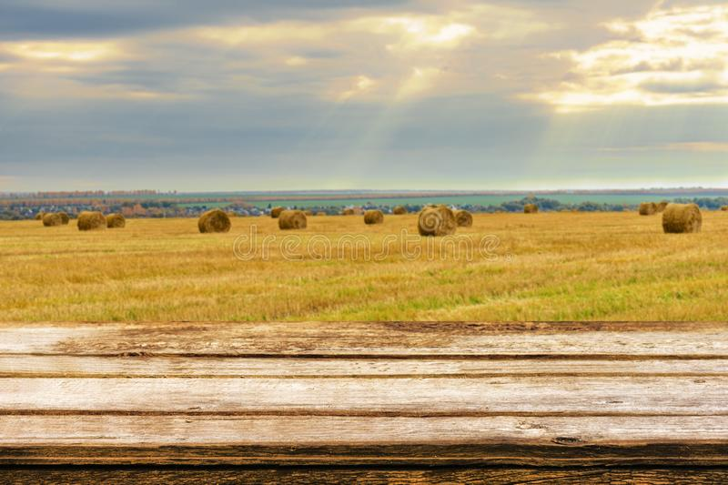 Empty wooden table with blurred autumn landscape of beveled field and straw bales. Mock up for display or montage products. Empty wooden table with blurred stock photos