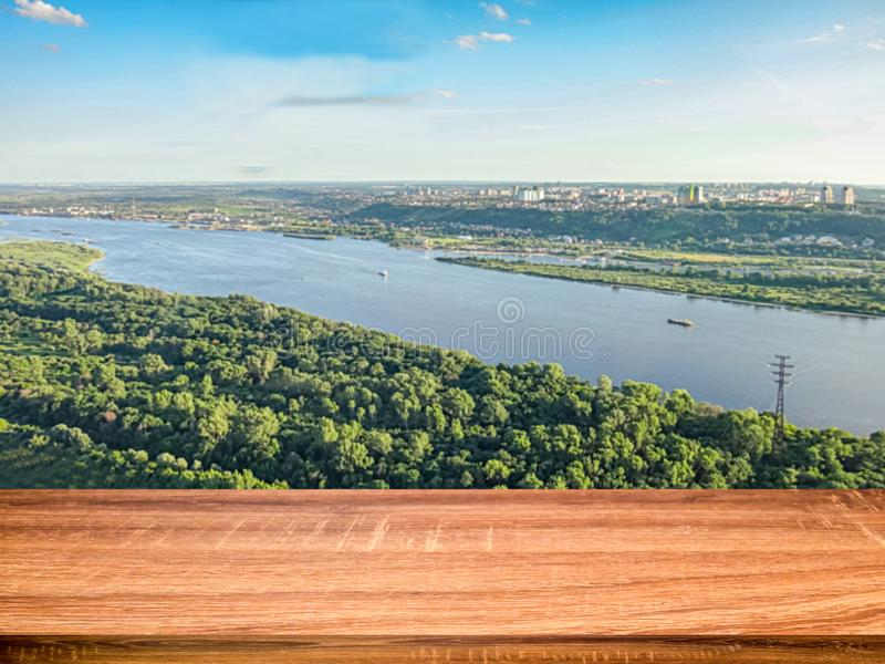 Empty wooden table with blurred background of aerial view of the Volga river and the Nizhny Novgorod city. Can be used for display stock photos