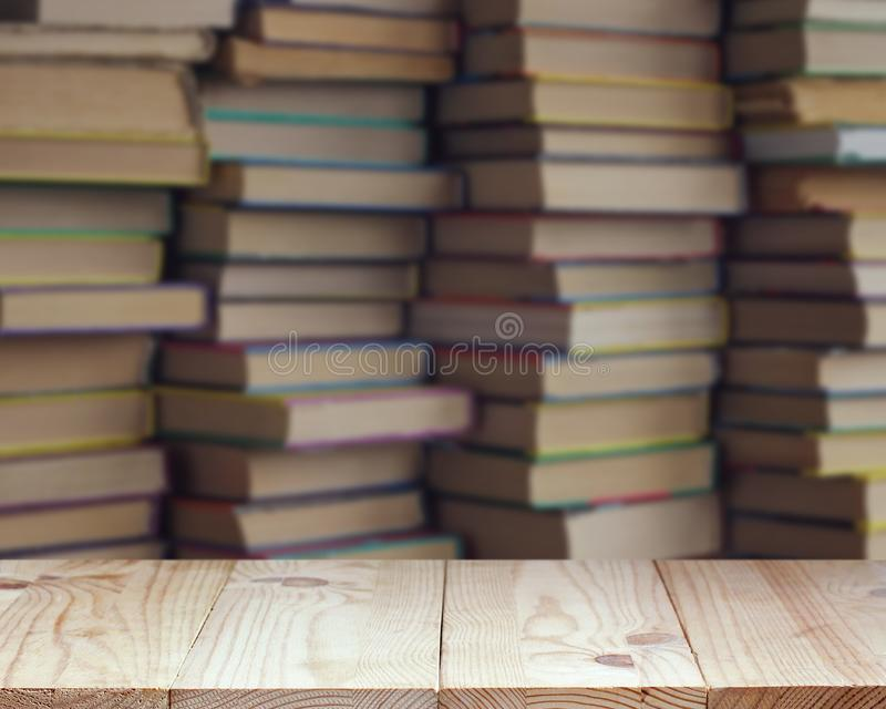 Empty wooden table on blurred background of books royalty free stock photo
