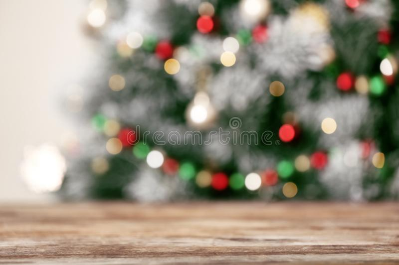 Empty wooden table and blurred fir tree with Christmas lights on background, bokeh effect. Space for design stock photography