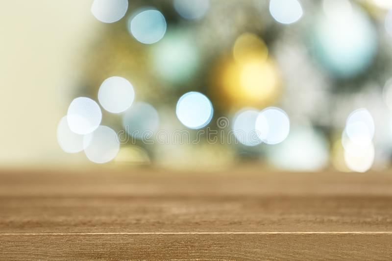 Empty wooden table and blurred fir tree with Christmas lights on background, bokeh effect. Space for design royalty free stock photo
