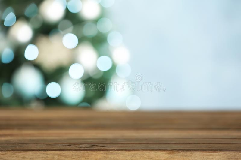 Empty wooden table and blurred fir tree with Christmas lights on background. Space for design. Empty wooden table and blurred fir tree with Christmas lights on royalty free stock image
