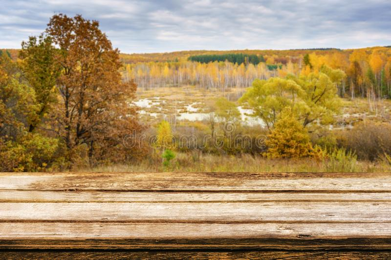 Empty wooden table with blurred picturesque autumn landscape of view from the hill to the lowland with forest and swamps. Mock up royalty free stock images