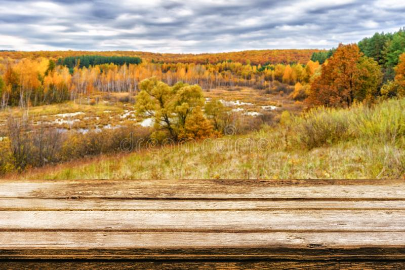 Empty wooden table with blurred picturesque autumn landscape of view from the hill to the lowland with forest and swamps. Mock up stock photo