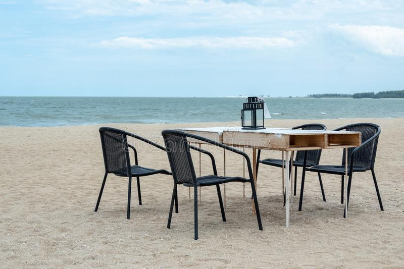 Empty wooden table and chair on the beach for family dinner with blue sea stock image