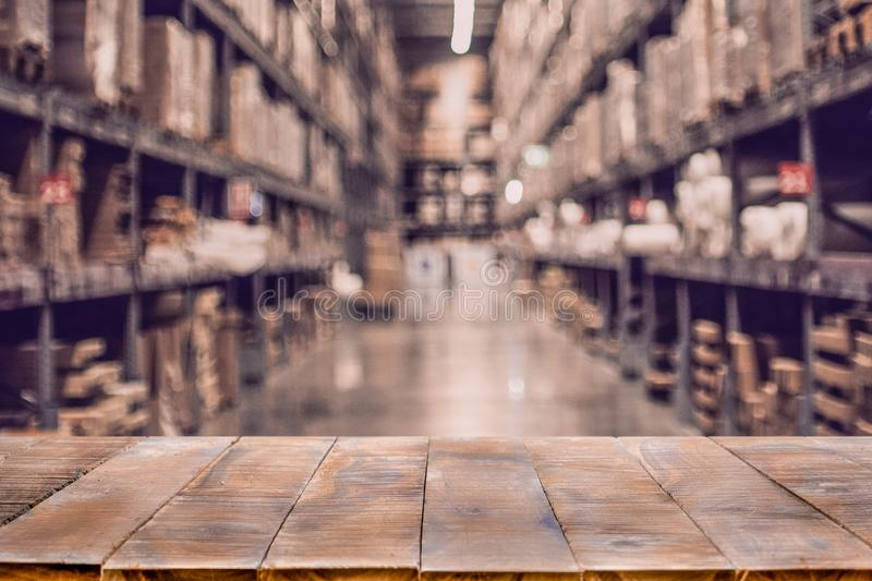Empty wooden table on defocused blurred boxes on rows of shelves stock photos