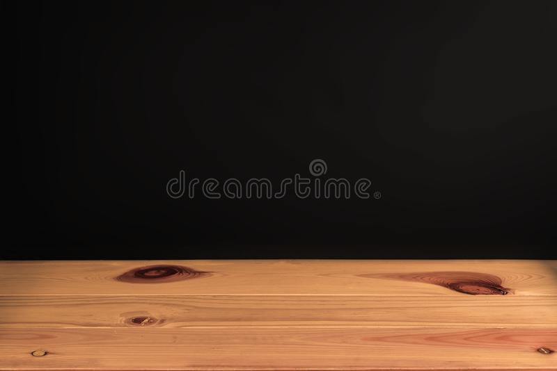 Wooden table or desk with black wall background in vintage tone. stock photo